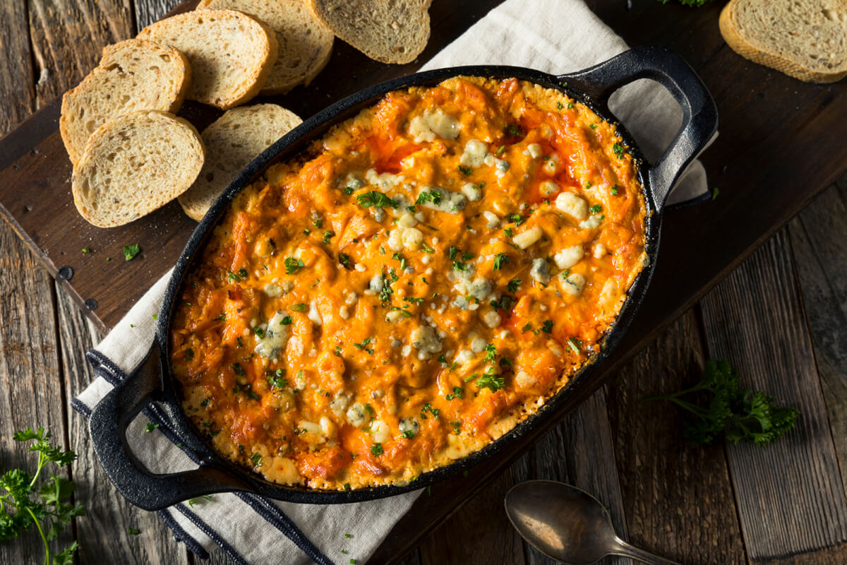 Buffalo chicken dip in a cast iron casserole sorrunded by toasted baguette slices.