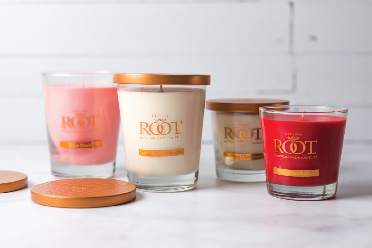 Group of pink and peach-colored candles in a glass jar by Root.