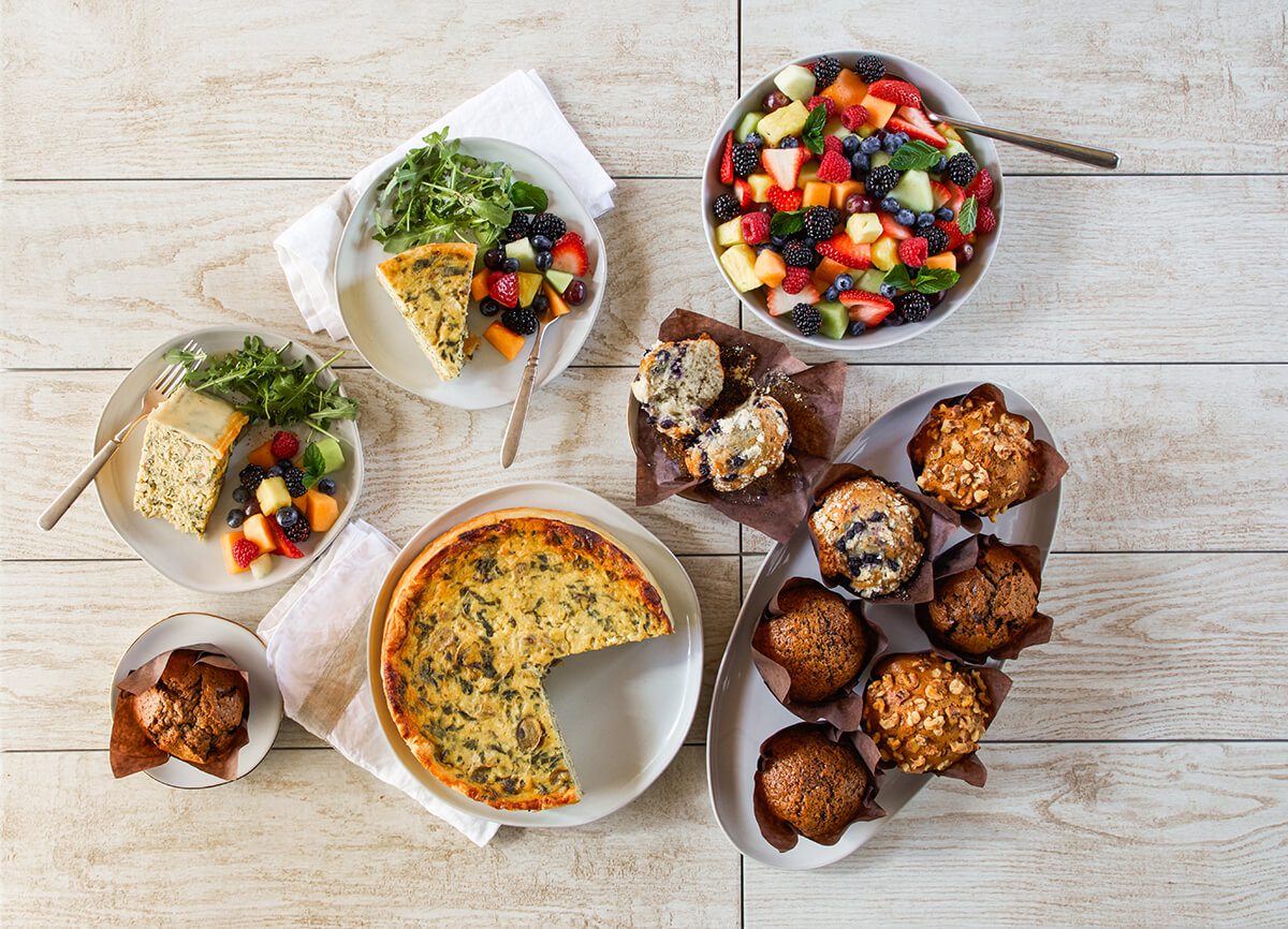 Quiche, fruit bowls, and muffins