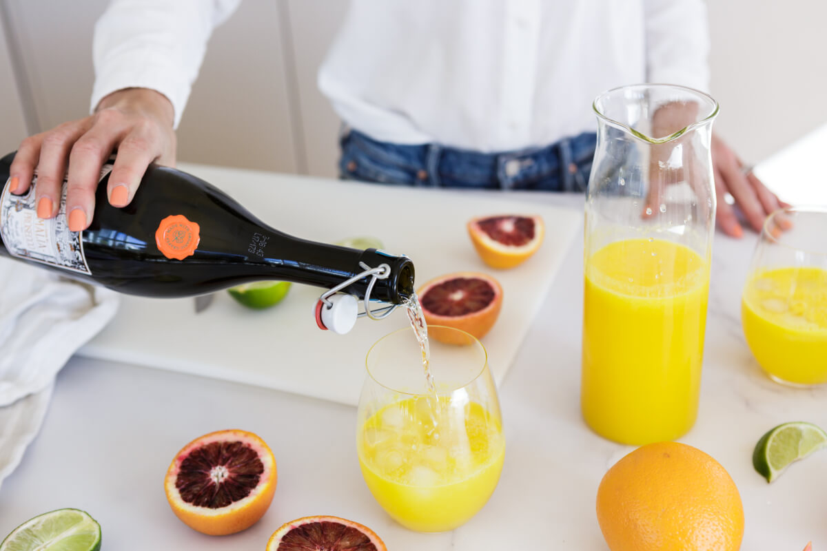 Champagne pouring into a glass of orange juice