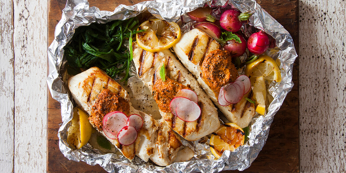 Grilled fish with lemon, spinach, and radishes