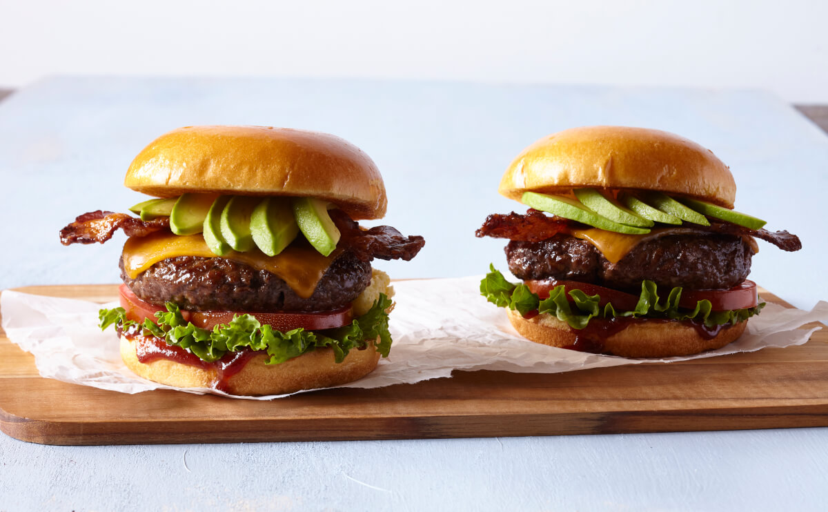 Burgers with avocado, bacon, cheese, tomato, and lettuce