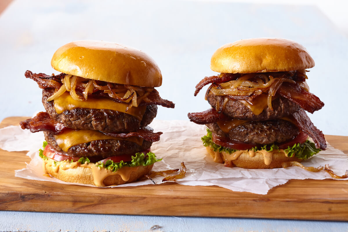 Two double bacon cheeseburgers hot off the grill, served on a wood plank with lettuce, tomato, cheddar cheese, and grilled onions.