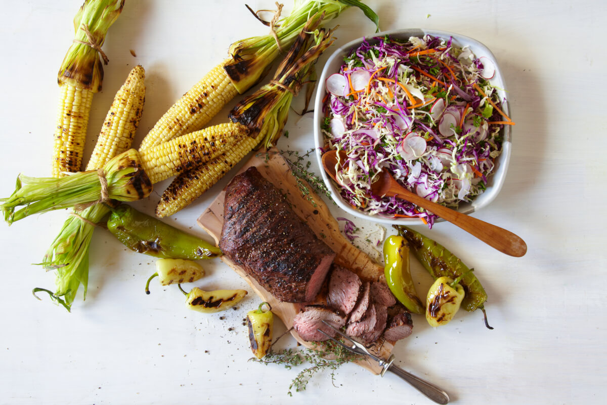 Bristol Farms Big Time Tri Tip on a wood board with freshly roasted corn, and a light coleslaw.