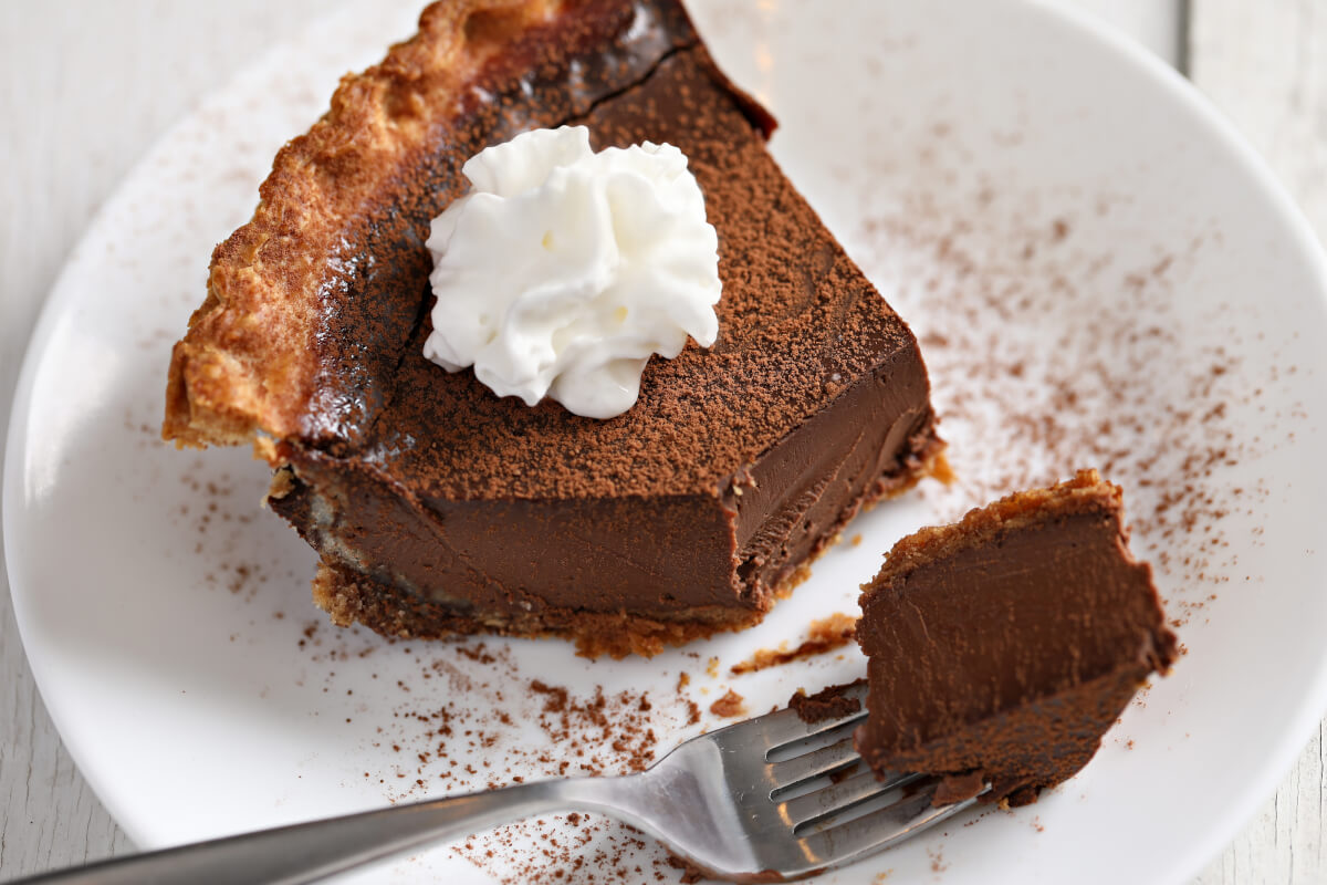 A tight shot of a chocolate pie with whipped cream and cocoa powder on white plate and white table with a piece taken out.