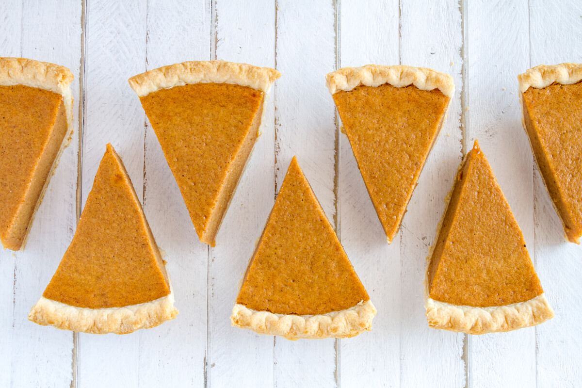 Slices of pumpkin pie on a white wood table.
