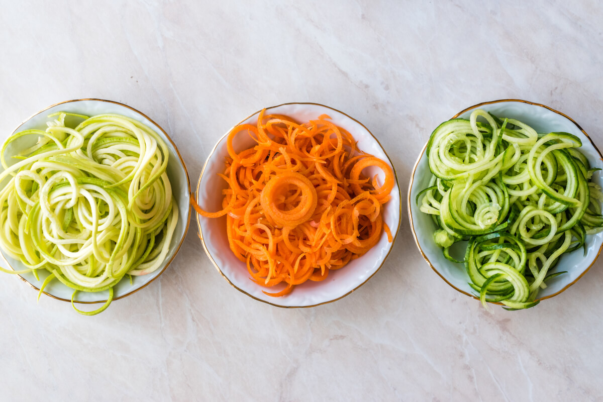 Sprialized carrots and zucchini in bowls overhead.