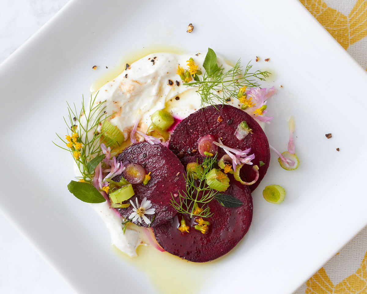 Three organic roasted beets on a bed of burrata cheese garnished with green onions, fresh herbs, and edible flowers with a drizzle of extra virgin olive oil.