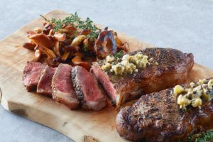 Rare cooked dry aged steak with mushrooms and blue cheese crumbles