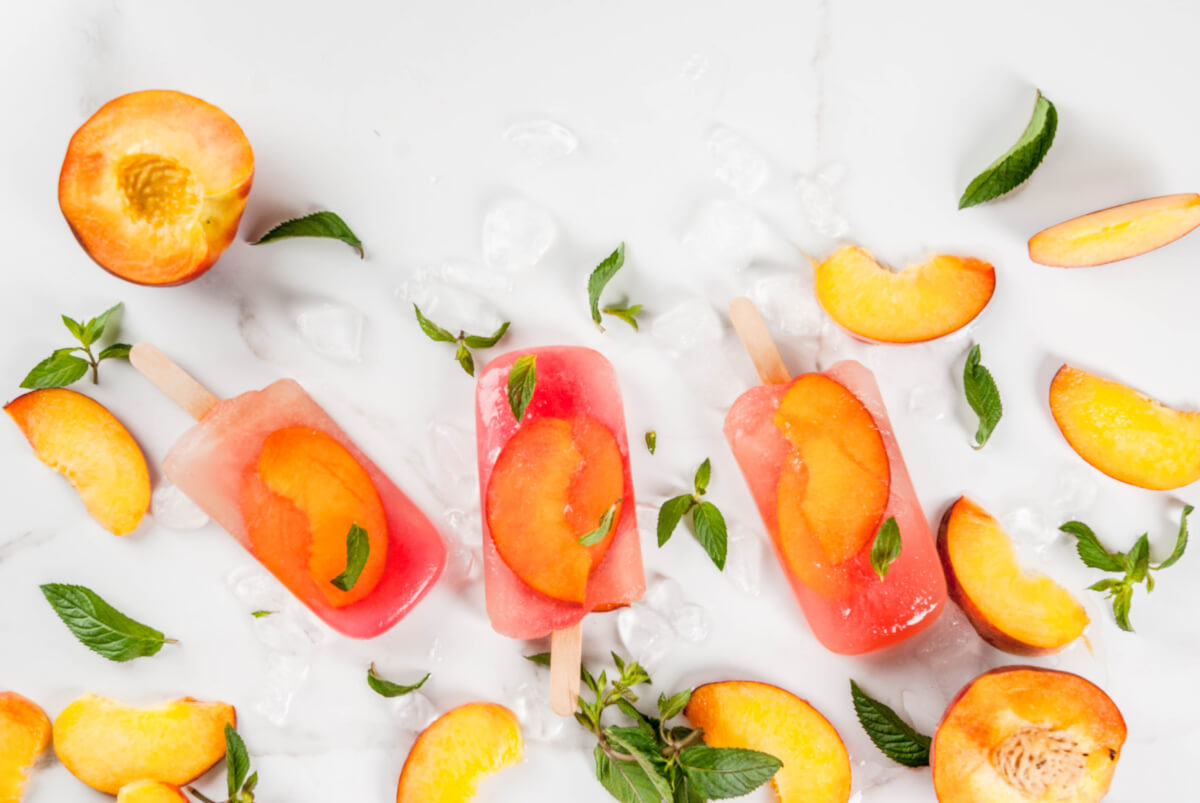 Three peach pops surrounded by fresh peaches, leaves, and ice on a white marble background.
