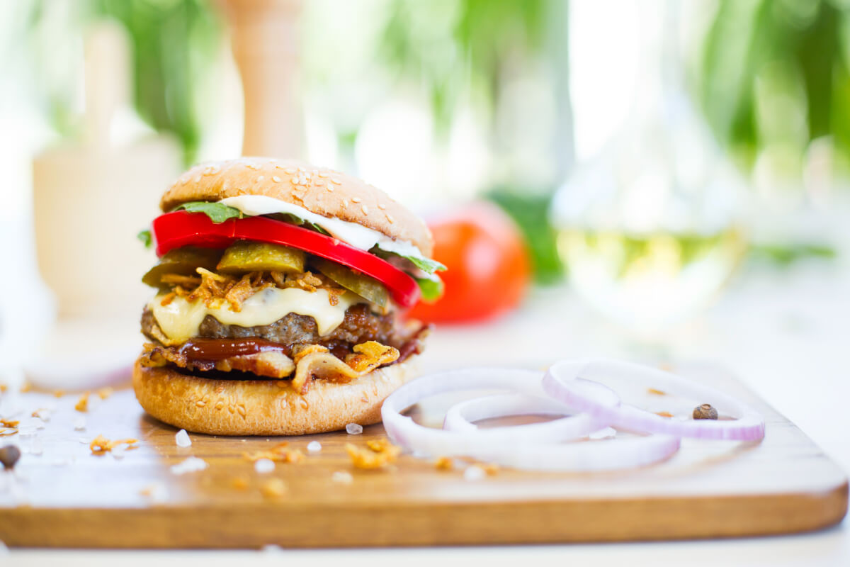 Cheeseburger with bacon and onion on wooden board.