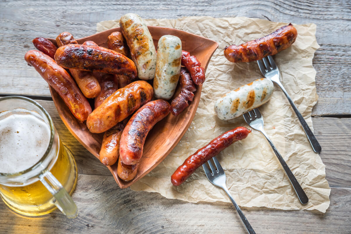 Beer and sausages on white wood table.
