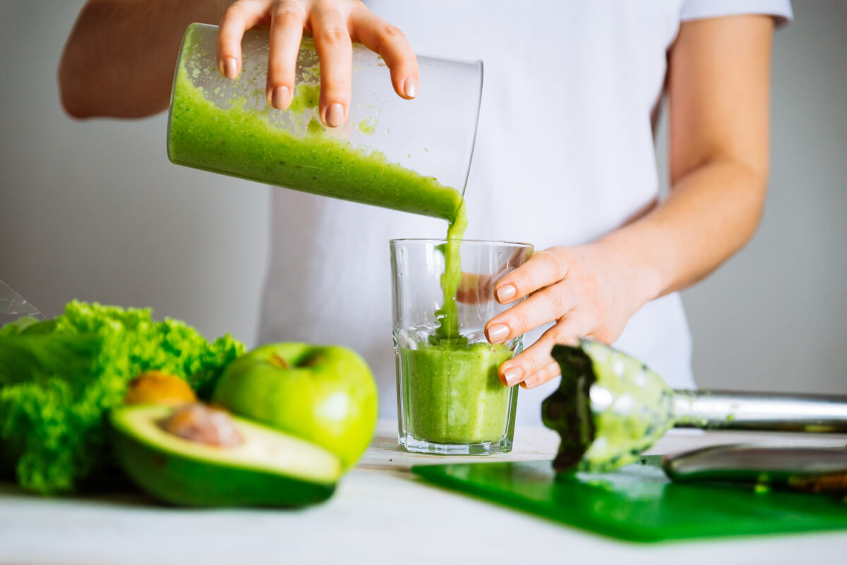 Woman pouring green juice into a cup.
