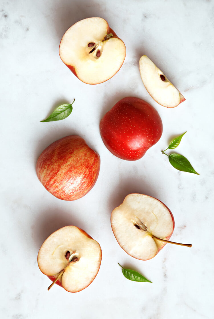 Apples on white marble background.