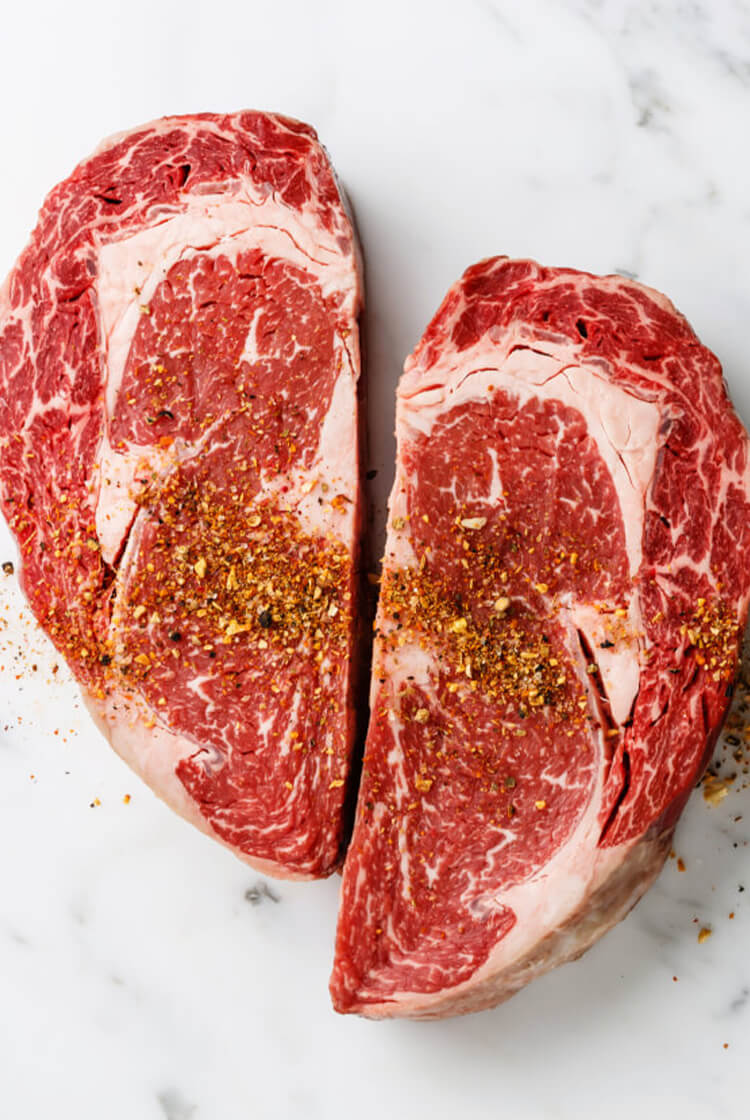 Heart-shaped dry-aged ribeye steaks on marble counter top.