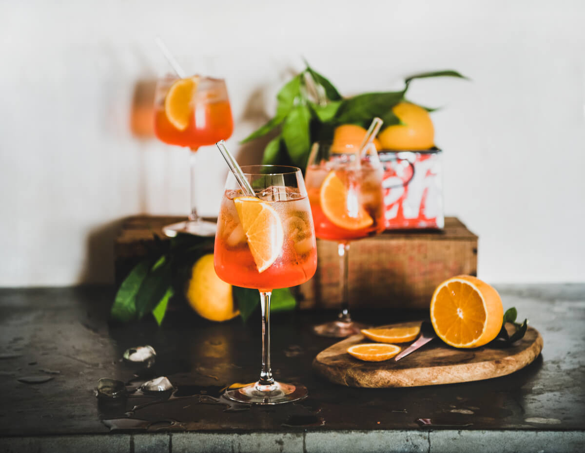 Three aperol spritz on a table with orange slices as garnishes.