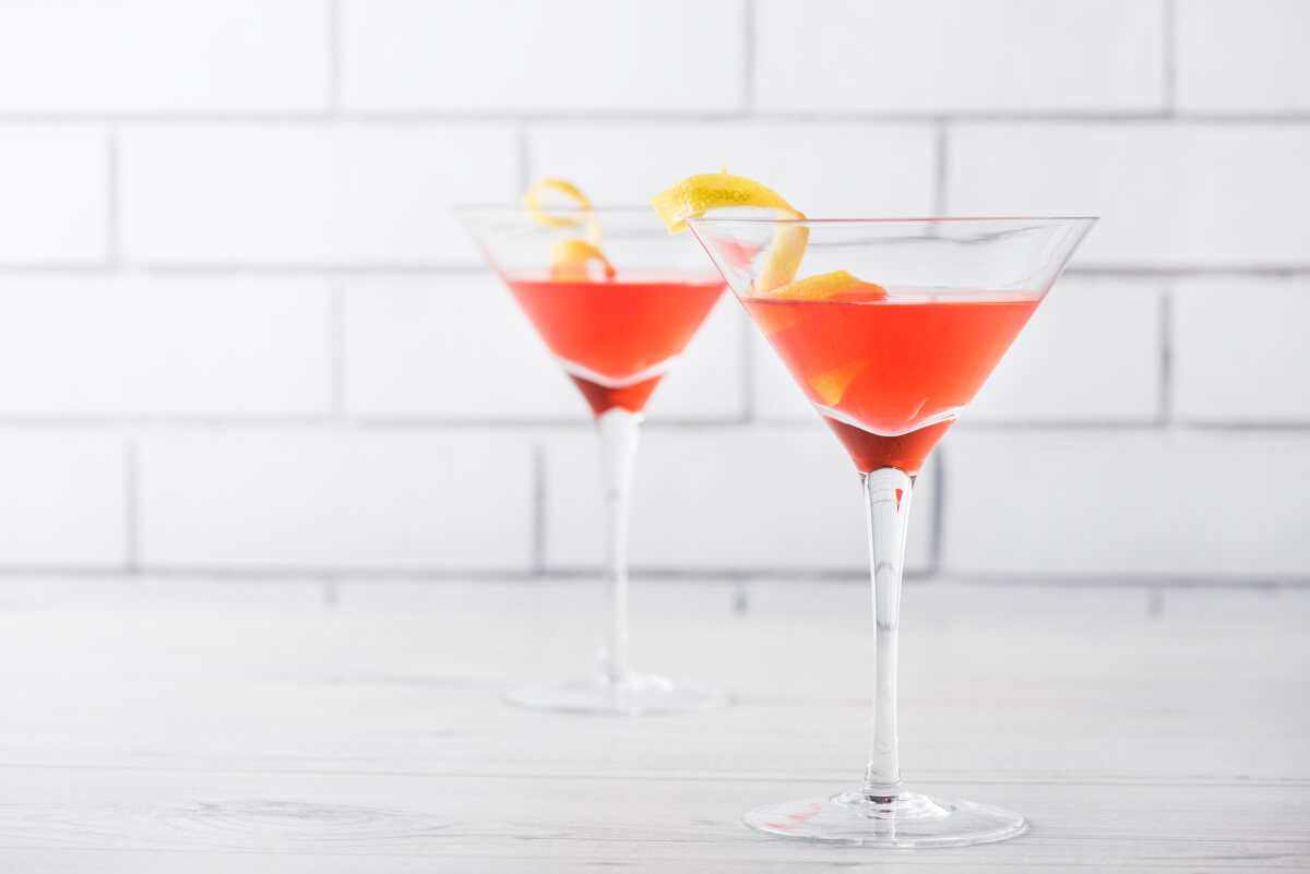 Two classic red cosmos with a twist of lime zest, on a white background and white table.