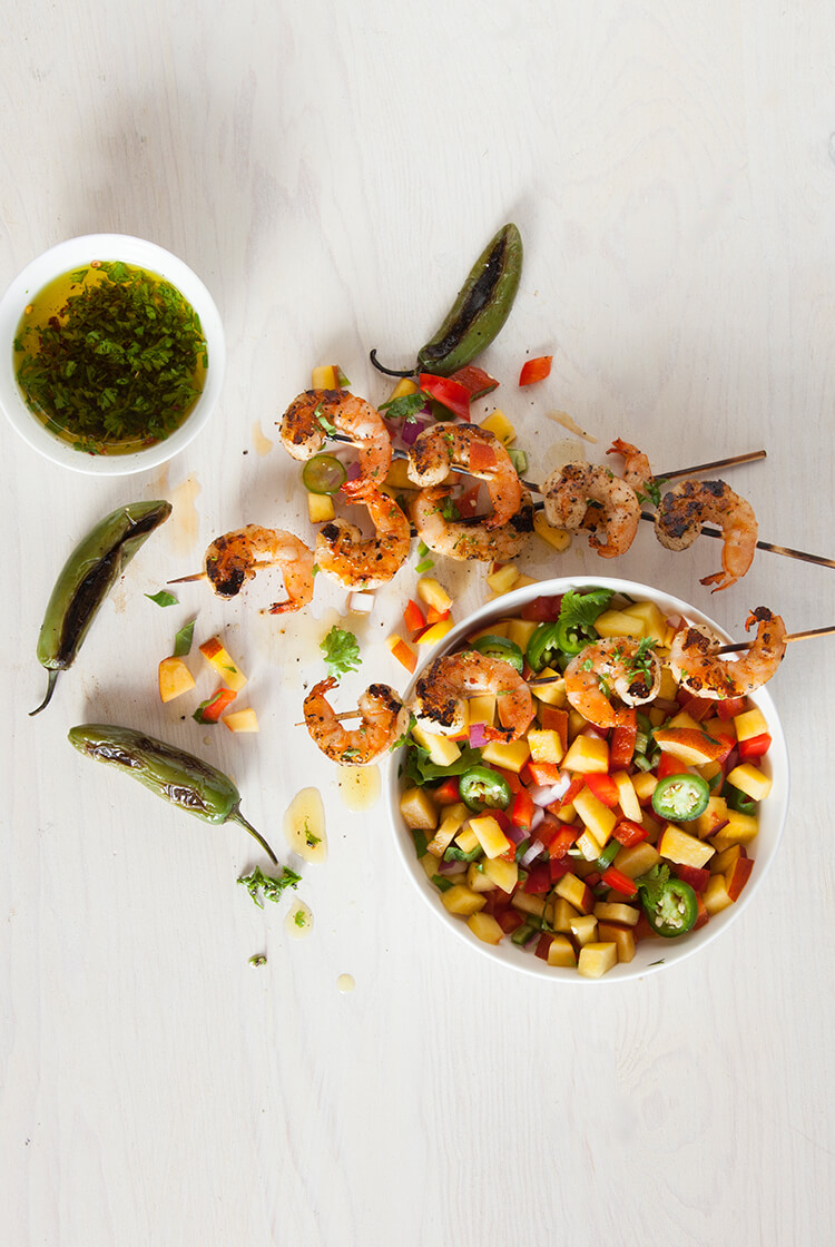 Grilled shrimp on skewers sitting on a bowl of peach salsa garnished with some blackened jalapenos and a spicy cilantro olive oil.