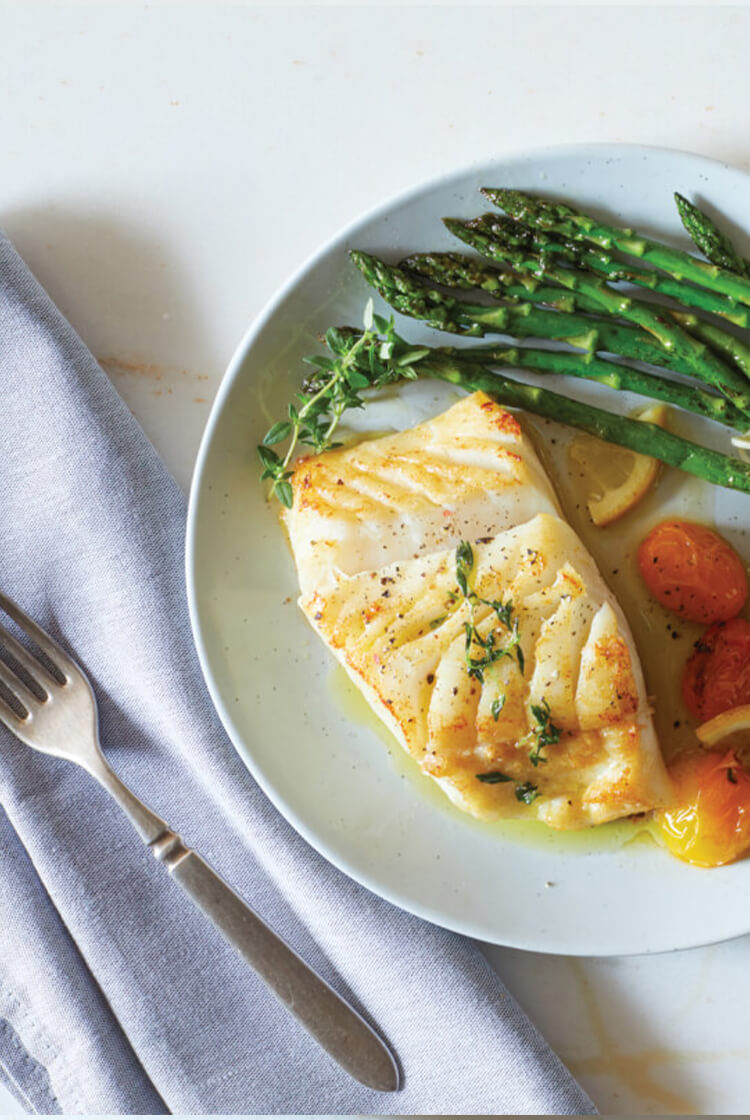 Lemon Baked Cod resting in extra virgin olive oil with blistered tomatoes and asparagus.