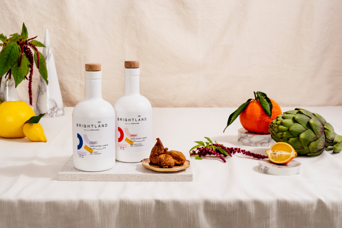 Brightland Olive Oil on a table with an orange