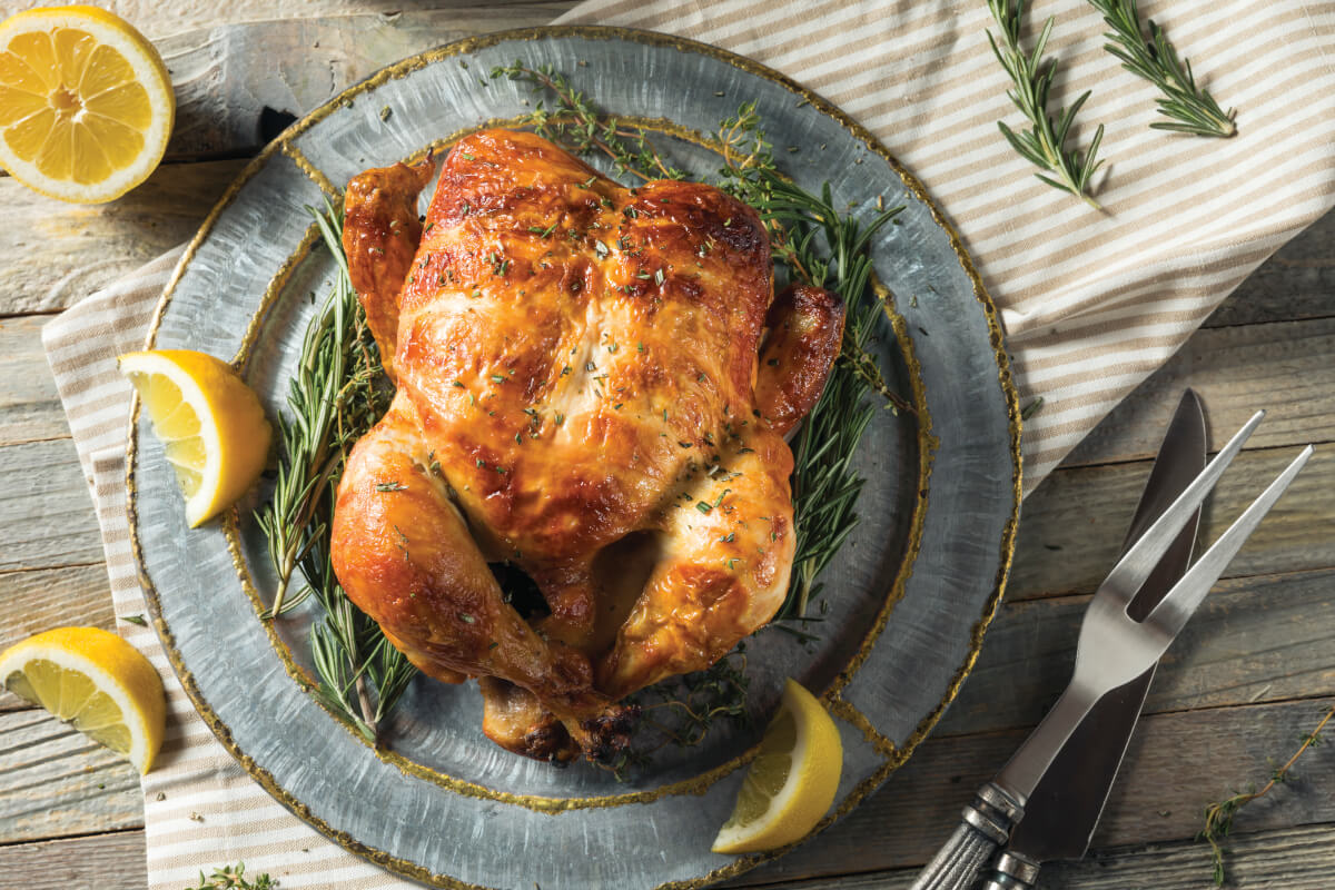 Roasted Chicken laying on a bed of rosemary and lemon wedges as a garnish.
