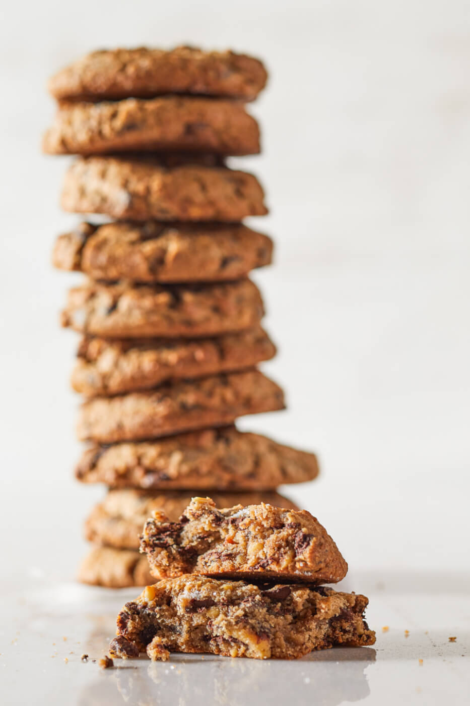 A large stack of Bristol Farms famous The Cookie are out of focus in the background. The foreground sits The Cookie broken in half to show off the chocolate chunks and toasted walnuts.