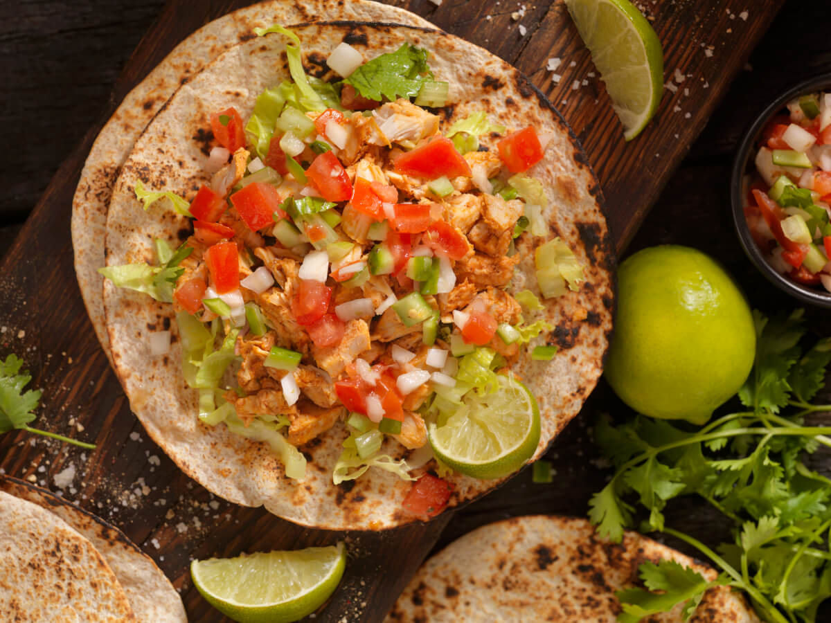 Pulled chicken tacos on a fresh tortilla with pico de gallo lemon and cilantro