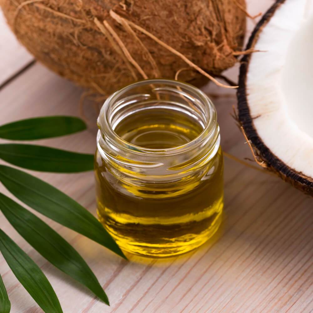 Coconut oil with coconuts and palm leaves