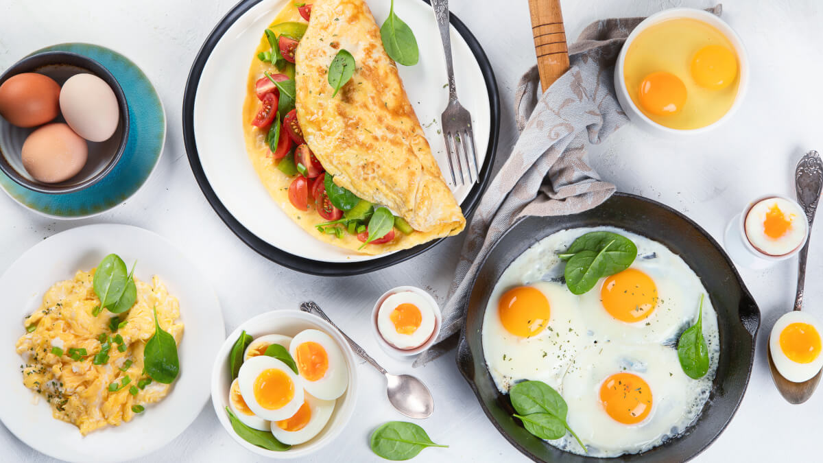 Omelette assortment on a table with eggs cracked open and omelette ingredients